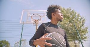 Zbliżenie portret młodego silnego amerykanin afrykańskiego pochodzenia męski gracz koszykówki rzuca piłkę w obręcz outdoors na zbiory wideo