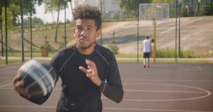 Zbliżenie portret młodego sporty amerykanin afrykańskiego pochodzenia męski gracz koszykówki rzuca piłkę w obręcz outdoors zbiory