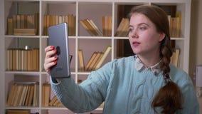 Zbliżenie portret młody ładny żeński uczeń ma wideo wezwanie opowiada emocjonalnie na pastylce w uniwersytecie zbiory