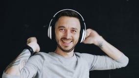Zbliżenie portret młody śmieszny mężczyzna stawia dalej hełmofony i szalonego tana podczas gdy słucha muzyka na czarnym tle Fotografia Stock