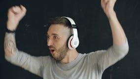 Zbliżenie portret młody śmieszny mężczyzna stawia dalej hełmofony i szalonego tana podczas gdy słucha muzyka na czarnym tle zbiory