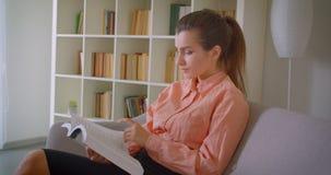 Zbliżenie portret młody atrakcyjny bizneswoman czyta książkowego obsiadanie na leżance w mieszkaniu indoors zbiory