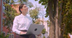Zbliżenie portret młody atrakcyjny caucasian bizneswoman używa laptop w parku outdoors w mieście zbiory