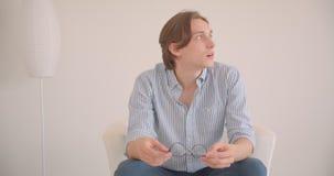 Zbliżenie portret młody atrakcyjny caucasian męski uczeń patrzeje kamerę trzyma jego eyeglasses siedzi w zbiory wideo