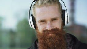 Zbliżenie portret młody brodaty modnisia mężczyzna z hełmofonami słucha muzyczny i ono uśmiecha się przy miasto ulicą zdjęcie wideo