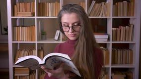 Zbliżenie portret młody caucasian żeński uczeń czyta książkę i ono uśmiecha się w szkłach szczęśliwie patrzejący kamerę wewnątrz zbiory wideo