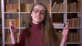 Zbliżenie portret młody caucasian żeński uczeń patrzeje kamerę wewnątrz w szkłach ma ona palce krzyżujący z nadzieją zbiory wideo