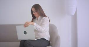 Zbliżenie portret młody caucasian bizneswoman w szkła działaniu na laptopu obsiadaniu na leżance indoors w zdjęcie wideo