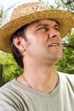 Zbliżenie portret młody człowiek z słomianego kapeluszu przyglądający up Obrazy Royalty Free