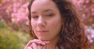 Zbliżenie portret młody kędzierzawy caucasian żeński uśmiechający się szczęśliwie patrzeje kamerę stoi outdoors w parku z zbiory wideo