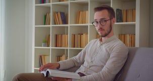 Zbliżenie portret młody przystojny caucasian biznesmen czyta książkę patrzeje kamerę uśmiecha się szczęśliwie siedzieć na zbiory wideo