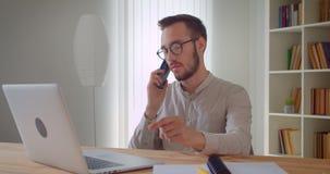 Zbliżenie portret młody przystojny caucasian biznesmen ma formalnego rozmowy telefoniczej obsiadanie przed laptopem zbiory wideo