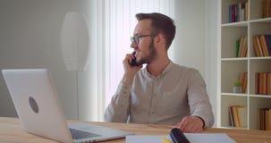 Zbliżenie portret młody przystojny caucasian biznesmen ma rozmowy telefoniczej obsiadanie przed laptopem indoors wewnątrz zbiory