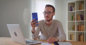 Zbliżenie portret młody przystojny caucasian biznesmen ma wideo wzywa telefon opowiada radośnie siedzieć wewnątrz zbiory