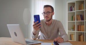 Zbliżenie portret młody przystojny caucasian biznesmen ma wideo wzywa telefonu obsiadanie przed laptopem zbiory wideo