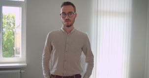 Zbliżenie portret młody przystojny caucasian biznesmen patrzeje kamerę indoors w mieszkaniu w eyeglasses zbiory
