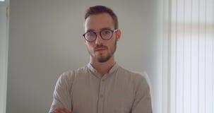 Zbliżenie portret młody przystojny caucasian biznesmen patrzeje kamerę z jego rękami w eyeglasses krzyżował zbiory wideo
