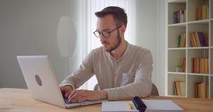 Zbliżenie portret młody przystojny caucasian biznesmen pisać na maszynie na laptopie patrzeje kamerę indoors w mieszkaniu zdjęcie wideo