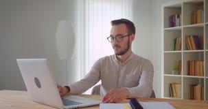 Zbliżenie portret młody przystojny caucasian biznesmen pisać na maszynie na laptopie patrzeje kamerę ono uśmiecha się pewnie zbiory wideo