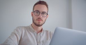 Zbliżenie portret młody przystojny caucasian biznesmen pisać na maszynie na laptopie patrzeje kamerę w eyeglasses zbiory