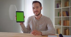 Zbliżenie portret młody przystojny caucasian biznesmen używa pastylkę i pokazywać zieleń ekran kamera indoors wewnątrz zbiory wideo