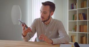 Zbliżenie portret młody przystojny caucasian biznesmen używa pastylkę i pokazywać zielonego chroma ekran kamera zdjęcie wideo