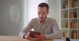 Zbliżenie portret młody przystojny caucasian biznesmen używa pastylkę patrzeje kamerę ono uśmiecha się szczęśliwie indoors wewnąt zbiory wideo