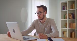 Zbliżenie portret młody przystojny caucasian biznesmen w eyeglasses ma wideo wzywa laptop indoors w zbiory