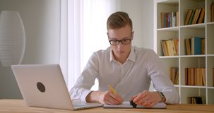 Zbliżenie portret młody przystojny caucasian biznesmen w szkłach używać laptop i brać notatkę indoors w zdjęcie wideo