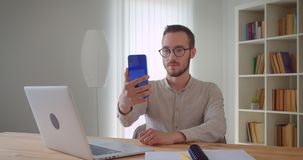 Zbliżenie portret młodzi przystojni caucasian businessmantaking selfies na telefonu obsiadaniu przed laptopem zbiory