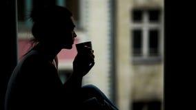 Zbliżenie portret Piękna kobieta przed okno z filiżanką Gorący napój w ranku Sylwetka zbiory
