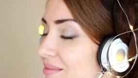 Zbliżenie portret piękna kobieta słucha muzyczna piosenka z oczami w hełmofonach zamykał w światłach zbiory
