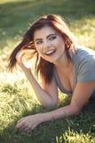 Zbliżenie portret piękna uśmiechnięta młoda Kaukaska kobieta z czerwonym czarni włosy, kłama na trawie Zdjęcie Royalty Free