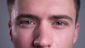 Zbliżenie portret piękny caucasian męski brąz przygląda się patrzeć prosto przy kamerą z zmieszanym wyrażeniem zbiory