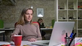 Zbliżenie portret pomyślny dorosły bizneswoman pisać na maszynie na laptopie cieszy się jej pracę w biurze obsiadanie plecy i zbiory wideo