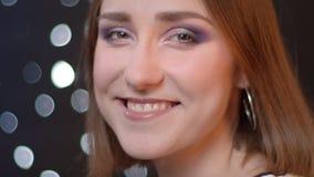 Zbliżenie portret potomstwo dziewczyny dosyć caucasian kręcenie, patrzeć kamerę i ono uśmiecha się z bokeh tłem zdjęcie wideo