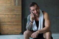 Zbliżenie portret przystojny mężczyzna wezwania telefon komórkowy w gym obrazy royalty free