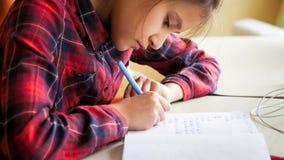 Zbliżenie portret skoncentrowany dziewczyny writing zadanie z piórem w copybook obrazy stock