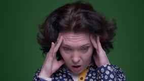 Zbliżenie portret stara caucasian brunetki kobieta ma migrenę i męczy przed kamerą z zdjęcie wideo