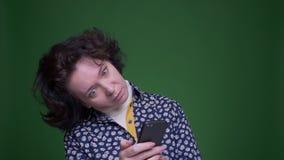 Zbliżenie portret stara caucasian brunetki kobieta używa telefon z tłem odizolowywającym na zieleni zdjęcie wideo