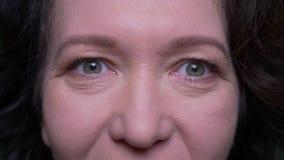 Zbliżenie portret starej caucasian brunetki żeńska twarz z oczami patrzeje kamerę z tłem odizolowywającym na zieleni zbiory