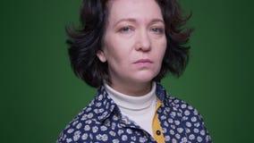 Zbliżenie portret starej caucasian brunetki żeński kręcenie i patrzeć kamerę z tłem odizolowywającym na zieleni zbiory