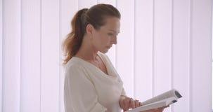 Zbliżenie portret starszy caucasian brunetka bizneswoman czyta książkę patrzeje kamery pozycję w bielu zdjęcie wideo
