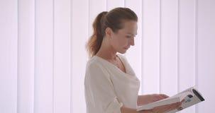 Zbliżenie portret starszy caucasian brunetka bizneswoman czyta książkową pozycję w białym biurze indoors zbiory