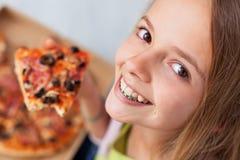 Zbliżenie portret szczęśliwa młoda nastolatek dziewczyna je plasterek o fotografia stock