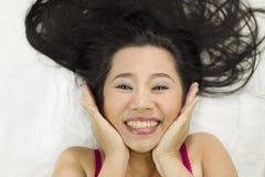 Zbliżenie portret szczęśliwe azjatykcie kobiety kłama na ziemi z czarny długie włosy działający uśmiech, zabawa fotografia stock