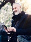 Zbliżenie portret szczęśliwego dorosłego atrakcyjnego biznesmena texting wiadomość na smartphone podczas gdy wydający czas w mias Zdjęcie Royalty Free