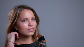 Zbliżenie portret uwodzicielski młody caucasian żeński patrzeć prosto przy kamerą i pozować zbiory wideo