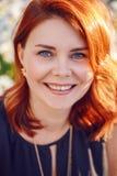 Zbliżenie portret w średnim wieku biała caucasian kobieta patrzeje w kamerze z zaondulowanym kędzierzawym czerwonym włosy w czern Fotografia Stock