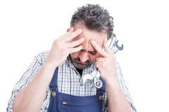 Zbliżenie portret w stresie młody mechanik mieć głowy ac zdjęcie stock